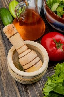 Widok z boku czarnego pieprzu w kruszarce czosnku z roztopioną oleistą sałatą, ogórkiem i solą pomidorową na drewnianej powierzchni