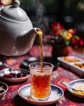 Widok z boku czarnej herbaty w szklanym kształcie gruszki na stole