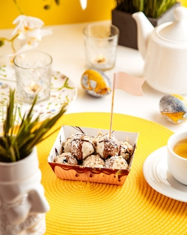 Widok z boku czekoladowych kulek z posypką kokosową i truskawką w kartonowej torbie