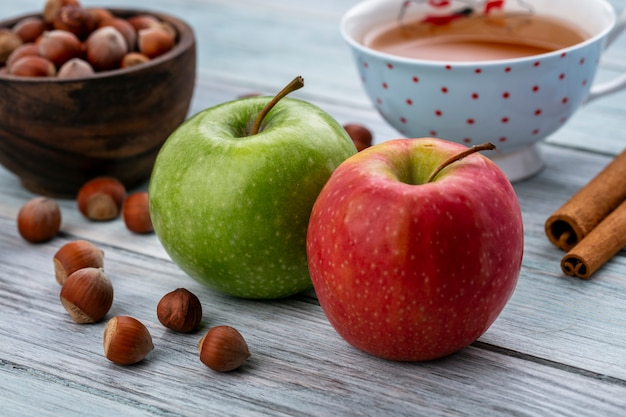 Widok z boku czerwone i zielone jabłko z filiżanką herbaty i cynamonem z orzechami na szarym tle