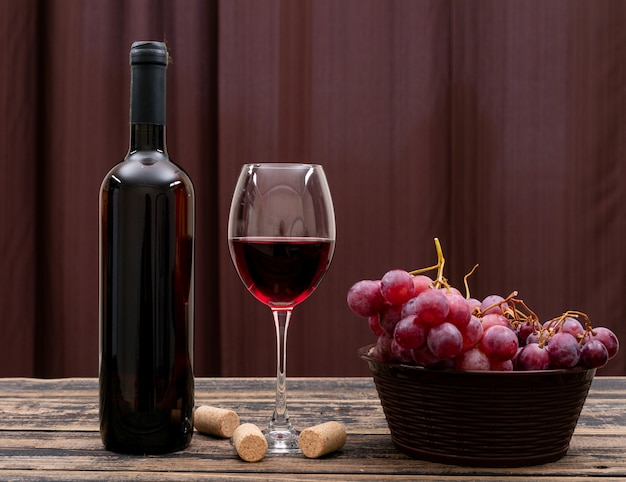 Widok z boku czerwone wino w butelce, szkle i winogronach na ciemnym stole i poziomych