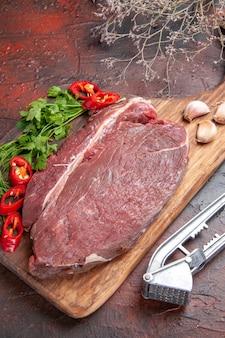 Widok z boku czerwonego mięsa na drewnianej desce do krojenia i posiekanej zielonej papryki czosnkowej na ciemnym tle