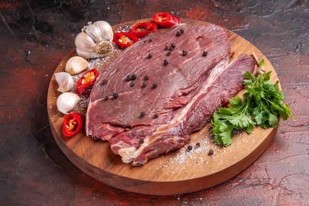 Widok z boku czerwonego mięsa na drewnianej tacy i czosnkowej zielonej cebuli cytrynowej na ciemnym tle