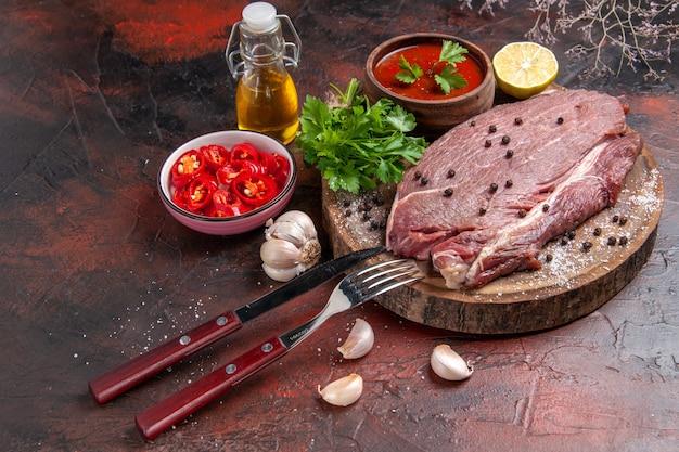 Widok z boku czerwonego mięsa na drewnianej tacy i zielonym keczupem z czosnkiem i posiekaną butelką oleju pieprzowego z cytryną na ciemnym tle