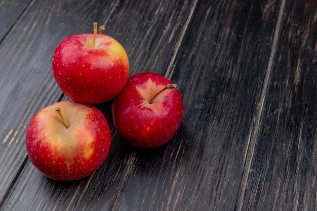 Widok z boku czerwonych jabłek na drewniane tła z miejsca kopiowania