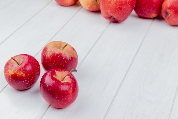 Widok z boku czerwonych jabłek na drewniane tła