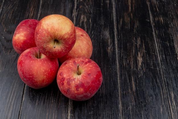 Widok z boku czerwonych jabłek na powierzchni drewnianych z miejsca na kopię