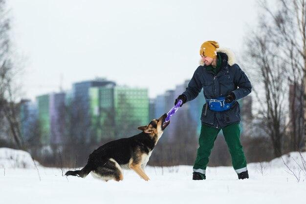 Widok z boku człowieka bawiącego się z psem pasterskim na zimowym polu