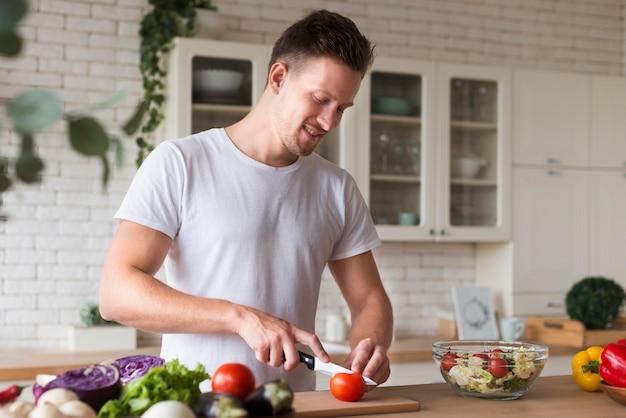 Widok z boku człowieka cięcia pomidora
