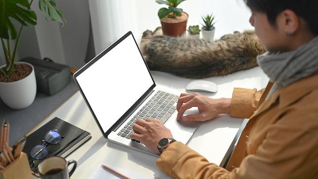 Widok z boku człowieka freelancer pracy na komputerze laptop siedząc ze swoim kotem w domu.