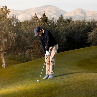 Widok z boku człowieka grającego na trawiastym polu golfowym
