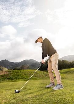 Widok z boku człowieka gry w golfa na polu z klubem i kopia przestrzeń