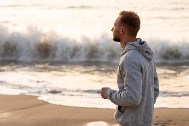 Widok z boku człowieka jogging na piasku