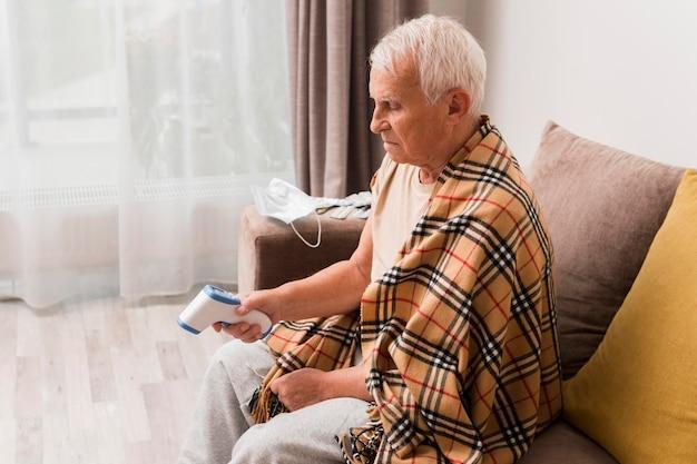 Widok z boku człowieka mierzącego temperaturę