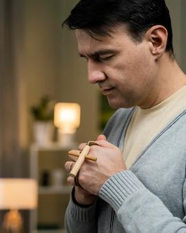 Widok z boku człowieka modlącego się z drewnianym krzyżem