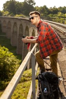 Widok z boku człowieka na moście z lornetką
