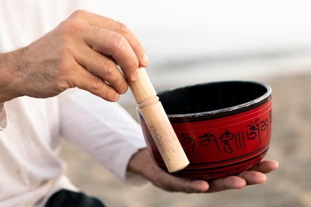 Widok z boku człowieka na plaży trzymając miskę do jogi