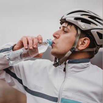 Widok z boku człowieka na rowerze górskim w specjalnym wyposażeniu