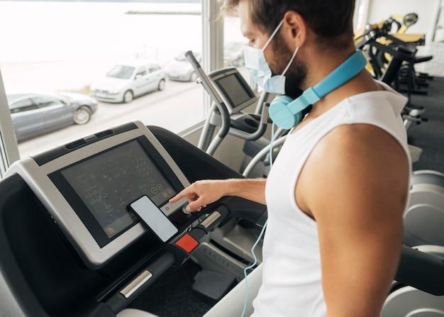 Widok z boku człowieka na siłowni przy użyciu bieżni