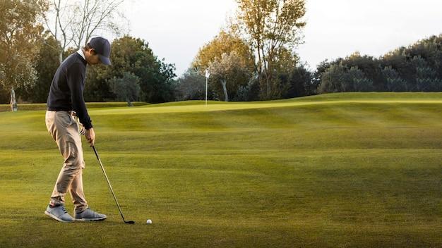 Widok z boku człowieka na trawiastym polu golfowym
