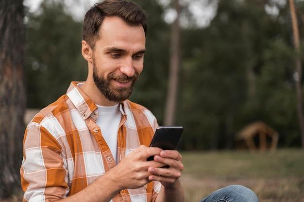 Widok z boku człowieka na zewnątrz, patrząc na smartfona