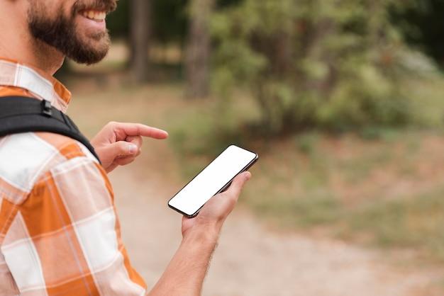 Widok z boku człowieka na zewnątrz trzymając smartfon