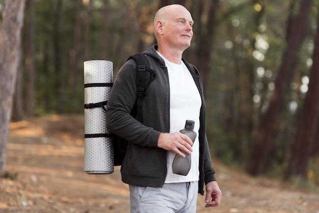 Widok z boku człowieka niosącego matę do jogi