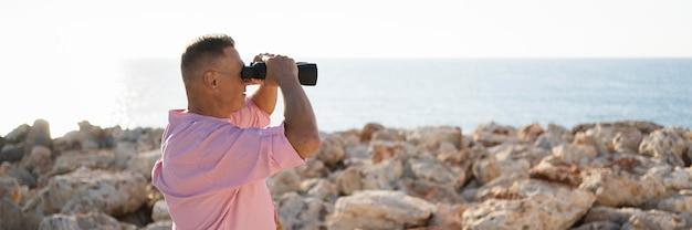Widok z boku człowieka oglądającego przez lornetkę