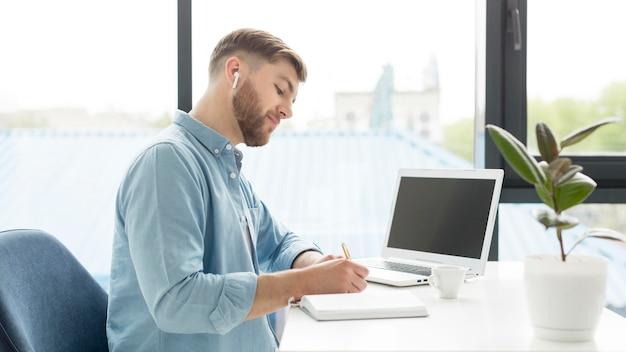 Widok z boku człowieka pisania w porządku obrad