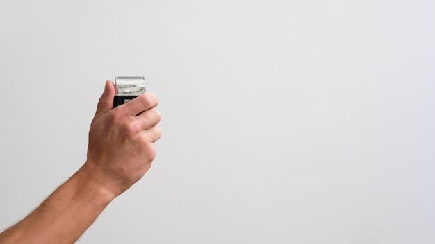 Widok z boku człowieka posiadającego golarkę elektryczną z miejsca na kopię