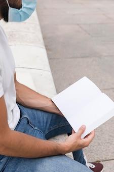 Widok z boku człowieka posiadającego książkę na zewnątrz podczas noszenia maski medycznej
