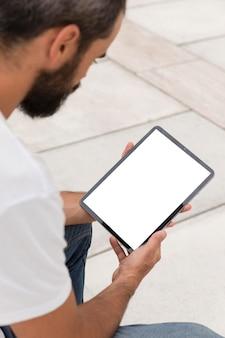 Widok z boku człowieka posiadającego tablet na zewnątrz