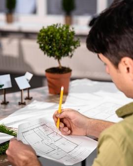 Widok z boku człowieka pracującego nad projektem ekologicznej energii wiatrowej z planami i ołówkiem