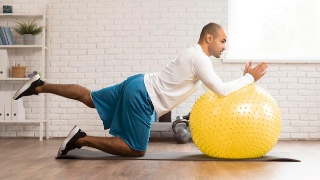Widok z boku człowieka robi fizjoterapii na piłkę