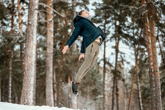 Widok z boku człowieka skaczącego na zewnątrz w przyrodzie zimą