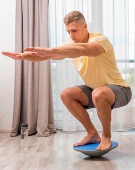 Widok z boku człowieka trenującego w domu przy użyciu piłki bosu