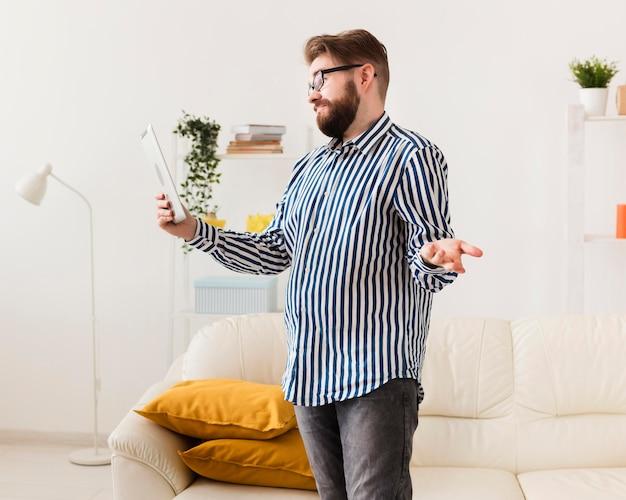 Widok z boku człowieka w domu z tabletem