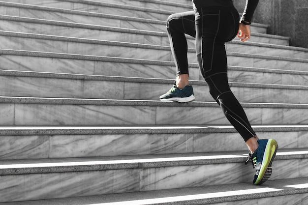 Widok z boku człowieka w lekkoatletycznej odzieży, ćwiczenia na schodach na zewnątrz