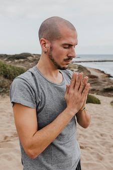 Widok z boku człowieka w pozycji medytacji na zewnątrz