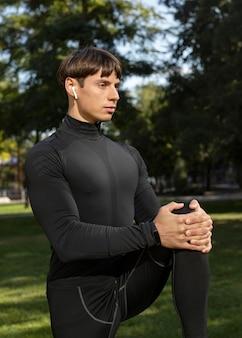 Widok z boku człowieka w sportowej odzieży i na zewnątrz słuchawek