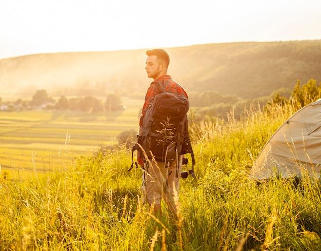 Widok z boku człowieka w zielonym polu z plecakiem