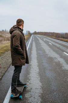 Widok z boku człowieka z deskorolką na drodze