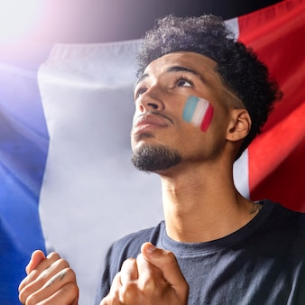 Widok z boku człowieka z flagą francuską, patrząc w górę i trzymając razem pięści