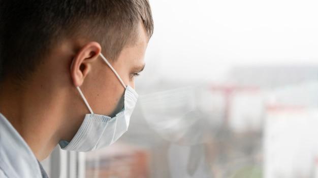 Widok z boku człowieka z maską medyczną, patrząc przez okno