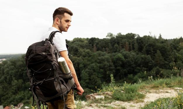 Widok z boku człowieka z plecakiem na drodze