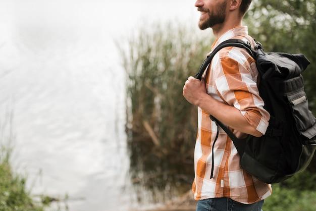 Widok z boku człowieka z plecakiem na zewnątrz