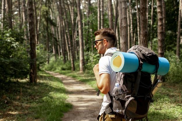 Widok z boku człowieka z plecakiem w lesie