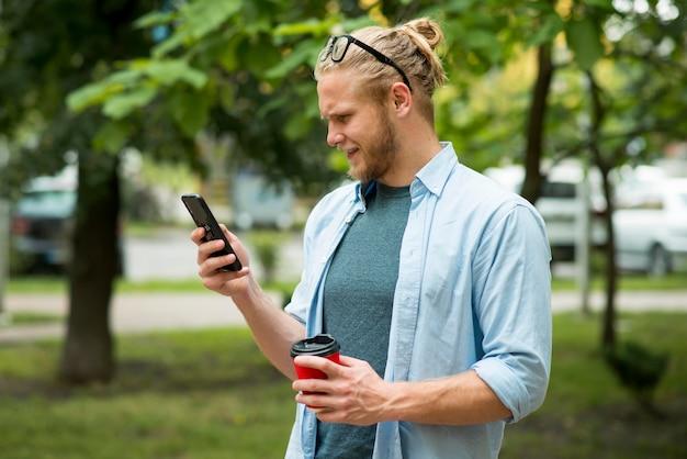 Widok z boku człowieka z telefonem i filiżanką na zewnątrz