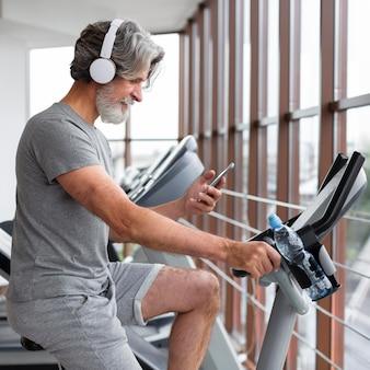 Widok z boku człowieka z telefonem na rowerze