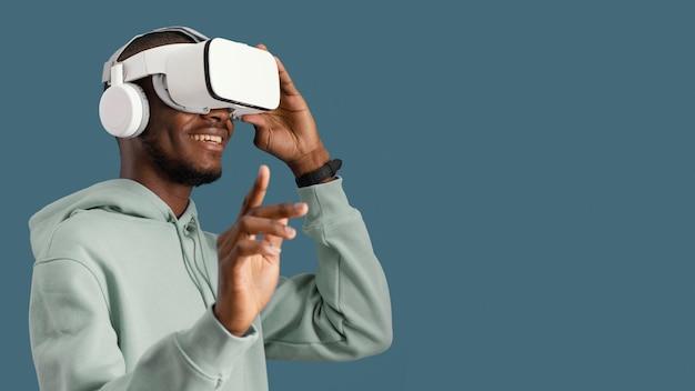 Widok z boku człowieka z zestawem słuchawkowym wirtualnej rzeczywistości i miejsca na kopię